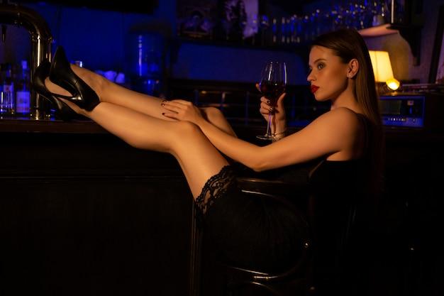 ワインのグラスを持つ美しい女性がバーに座っています。