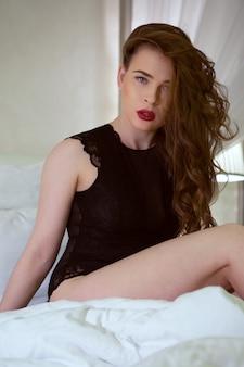 ボディースーツでベッドの上に座っている美しい若い女性