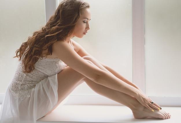 窓辺に座っている白いランジェリーの少女