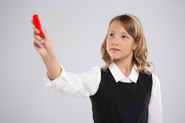 女の子女子高生は赤いチョークでボードに書き込みます。
