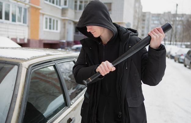 Молодой хулиган в черной куртке с бейсбольным мячом пытается разбить окно машины.