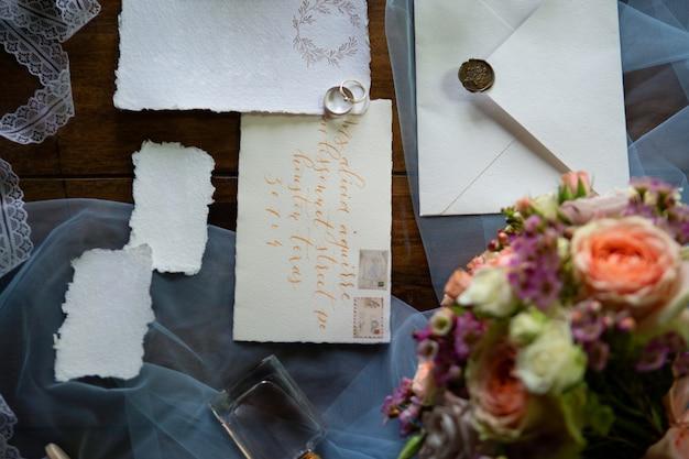 結婚式の装飾と木製のテーブルのアクセサリー。色付きのリボンとジュエリーで飾られた結婚式のアクセサリーのセット