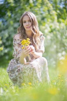 花を集めて座っている魅力的な女の子