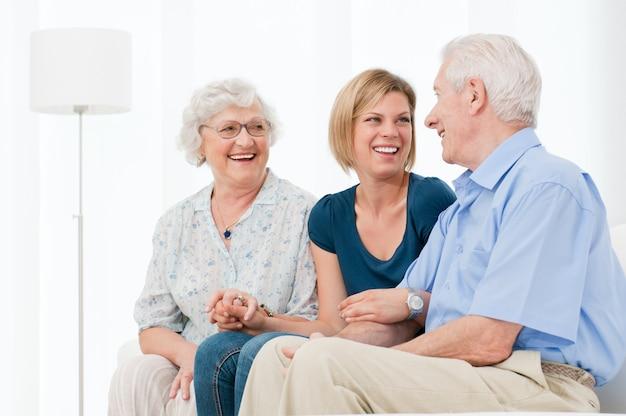 幸せな笑顔の孫娘が自宅で祖父母との時間を楽しむ