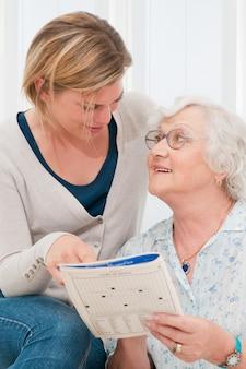 自宅で若い孫娘の助けを借りてクロスワードパズルを解くシニア女性