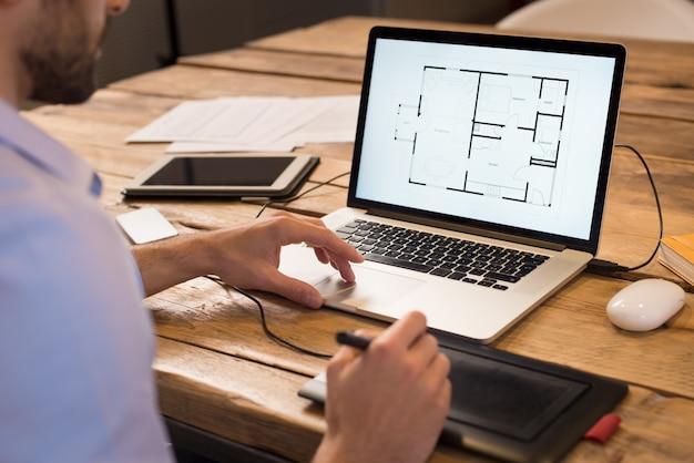 オフィスで働く若いインテリアデザイナーのクローズアップ。グラフィックタブレットで新しい家のプロジェクトでラップトップに取り組んでいる建築家。コンピューターで彼の家のプロジェクトのレイアウトを勉強しているインテリアデザイナー。