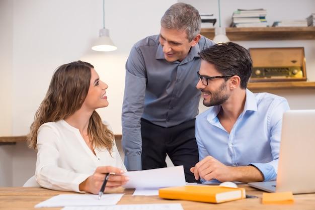 オフィスで新しい研修生と対話するシニアマネージャー。オフィスの幹部との会話で若い笑顔の従業員。リーダーとオフィスで笑って幸せなビジネスチームワーク。