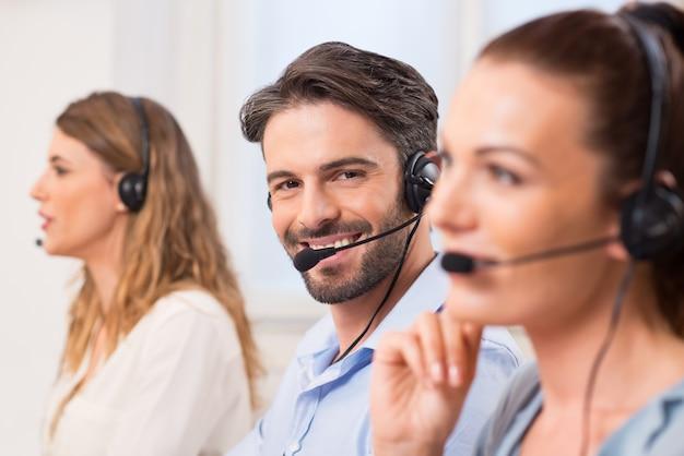 笑って幸せな電話オペレーターの肖像画。コールセンターで同僚と一列に並んでいるうれしそうなエージェント。連続して働く幸せな電話オペレーターのクローズアップ。