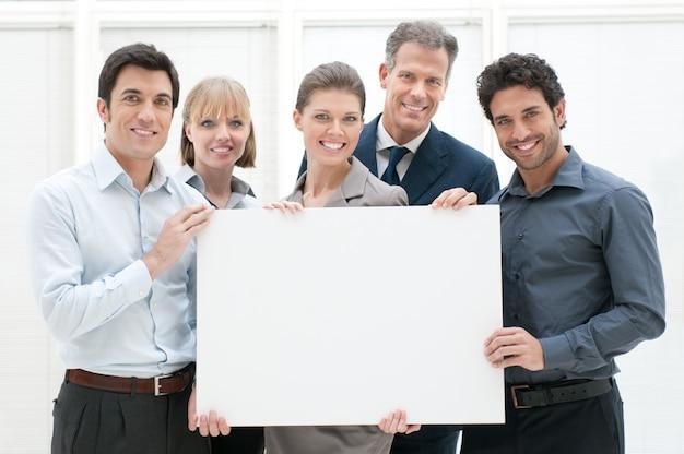 テキストまたは製品の準備ができている空白のプラカードを持って幸せな笑みを浮かべて事業チーム