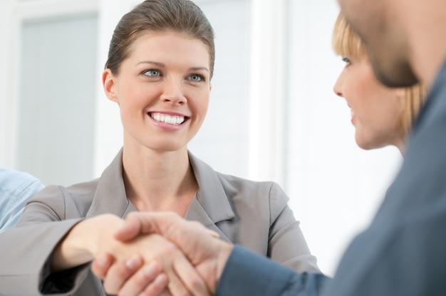 ビジネス会議の後握手して幸せな笑みを浮かべてビジネス女性