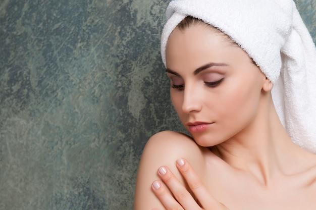 美容治療後の彼女の柔らかい肌に触れる美しい若い女性
