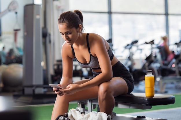 Женщина с помощью телефона в тренажерном зале