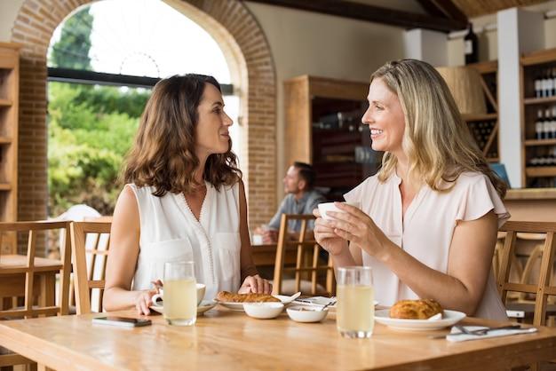 Женщины разговаривают за кофе