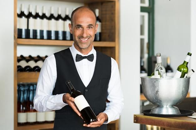 ワインのボトルを保持しているソムリエ