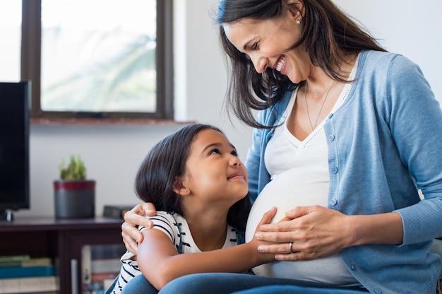 Дочь трогает живот своей беременной матери
