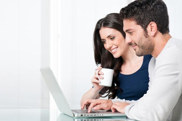 Улыбающаяся пара с ноутбуком