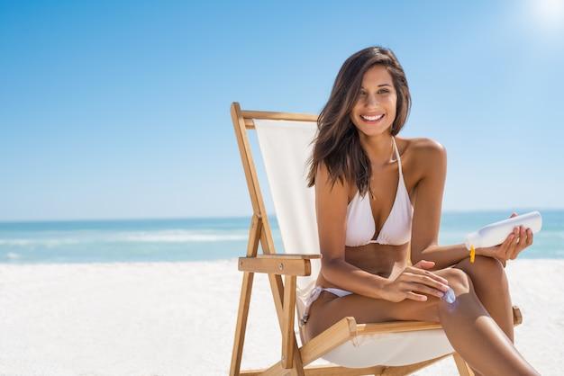 Женщина прикладывая солнцезащитный крем