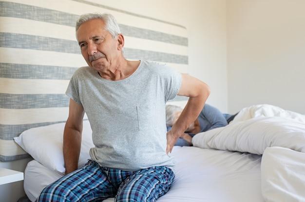 背中の痛みに苦しんでいる老人
