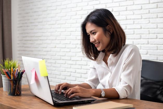ホームオフィスの木製の机の上の若いアジア女性作業ラップトップコンピューター
