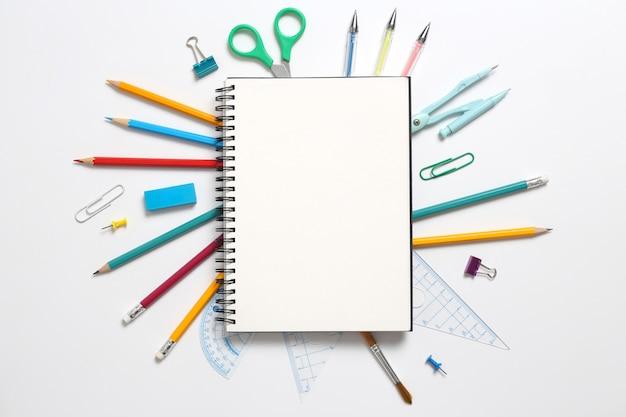 上面図、白い背景の上の空のノートブックおよび学校用品