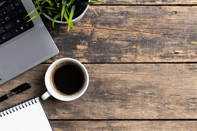 トップビューの作業スペース、コーヒーとコンピューターのあるオフィスデスク、コピースペースのある事務用品