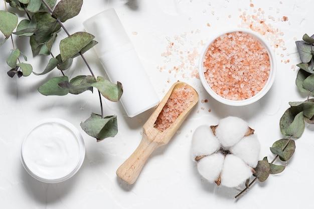 Натуральные косметические средства для ухода за ванной и кожей с ветками эвкалипта и хлопка цветы на белом фоне вид сверху.