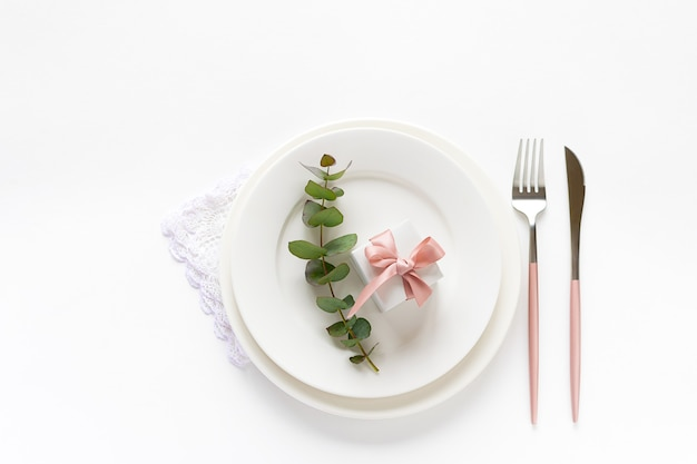 Праздничная сервировка для романтического ужина с подарочной коробке на тарелку, столовые приборы эвкалиптовых веток на белом фоне.