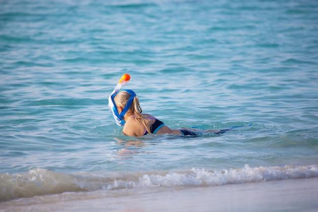 若い女性が海でシュノーケリングに行く
