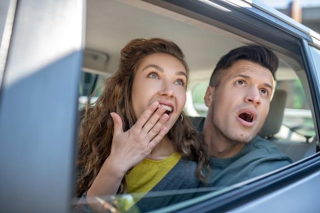Очень удивлены мужчина и женщина, глядя из машины