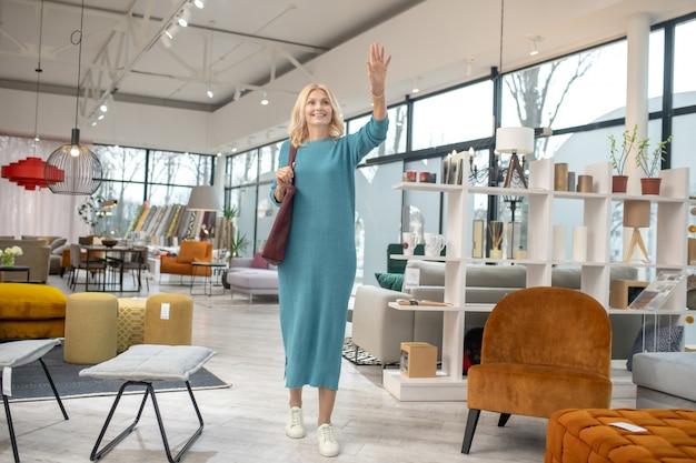 立っていると手を振っている青いドレスのブロンドの女性
