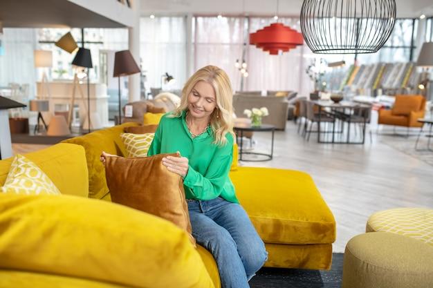 枕を保持しているグリーンのブラウスに金髪の女性