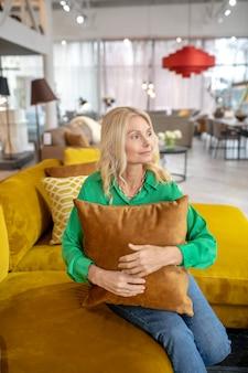 枕と座っている緑のブラウスに金髪のきれいな女性