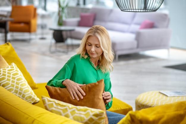 枕に触れる緑のブラウスに金髪の女性
