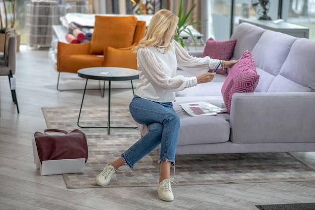 Женщина в белой блузке и джинсах сидит на диване, фотографируя розовую подушку с рисунком на смартфоне в мебельном салоне.