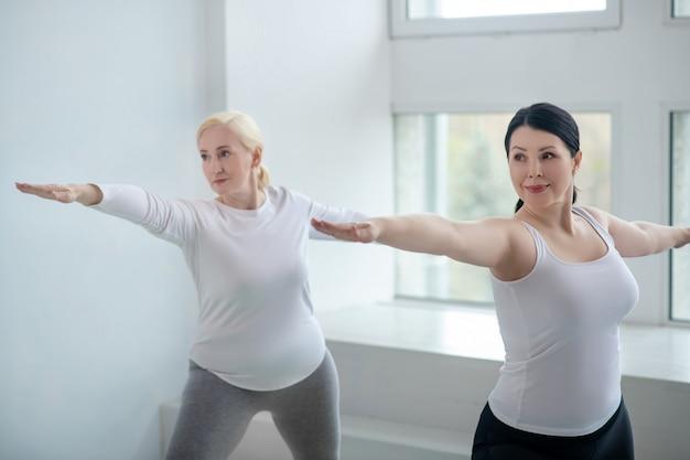 Практика йоги. брюнетка и блондинка стоя в позе воина с руками, параллельными полу