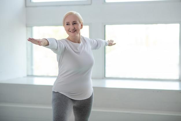 Практика йоги. зрелая блондинка стоит в позе воина с руками, параллельными полу