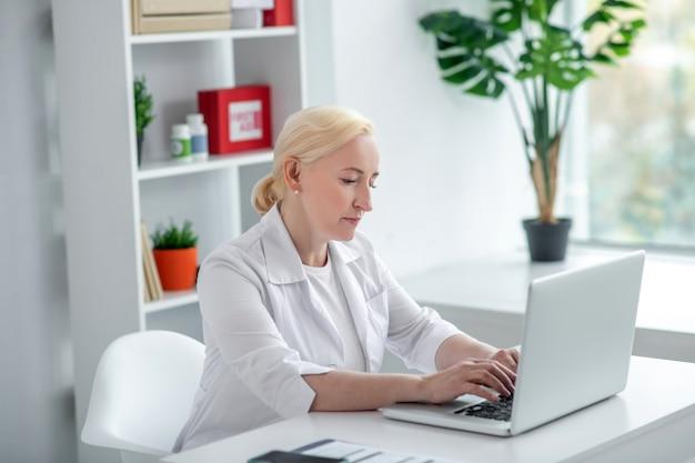 遠隔医療。彼女の机に座ってオンラインで患者と話している金髪の中年開業医