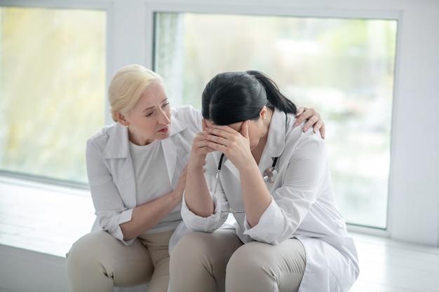 Чувствую себя подавленным. брюнетка-доктор в депрессии, ее коллега выглядит обеспокоенной