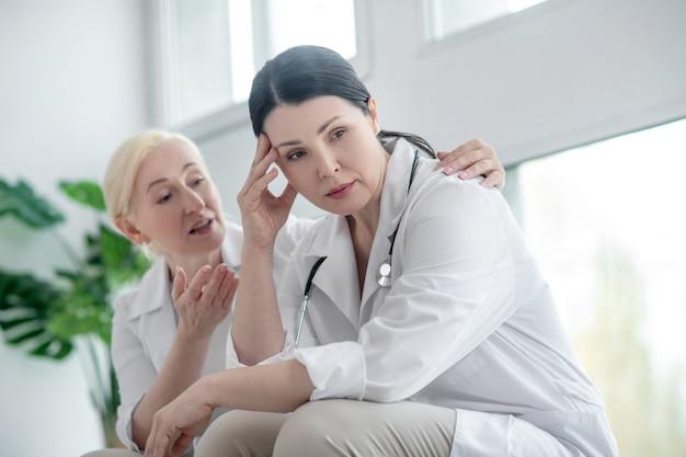 悪いニュース。欲求不満に見えるブルネットの医者、心配そうに見える彼女の同僚