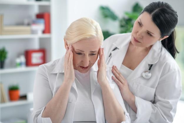 Головная боль. блондинка доктор держит ее голову и страдает от головной боли, ее коллега выглядит обеспокоенным