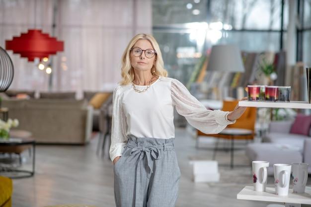 ショップのインテリア。店の大きなホールで、皿と彼女のポケットに手を入れて、ラックの近くに立っている眼鏡をかけた深刻な金髪の女性。