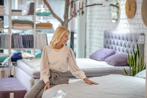 家具、ベッド。店の新しいベッドの上に座って、彼女を見て、幸せな笑顔で肩の長さの髪のきれいな女性