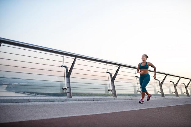 走っている女性。朝は橋の上を走っている太った浅黒い肌の女性