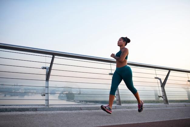 朝のランニングを楽しんでいます。街で朝のランニングを楽しむレギンスを着ている浅黒い肌の女性