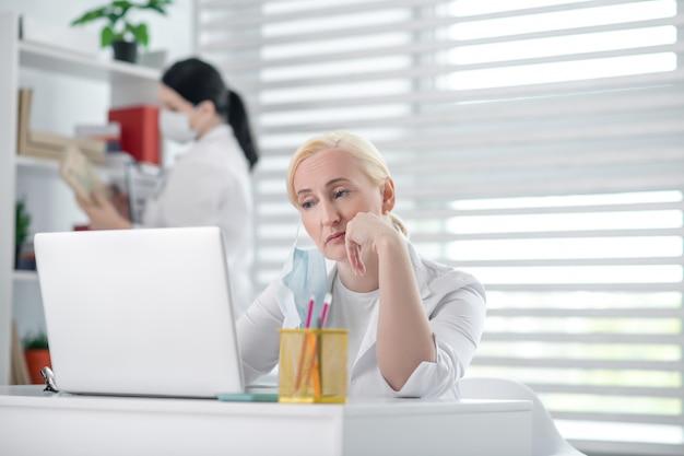 ハードな日。棚の近くに立っている防護マスクでラップトップ、黒髪の同僚に座って疲れている金髪の女性医師。