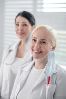 女性医師。窓辺に立っている仮面をつけた白いガウンを着た黒髪と金髪の女性。