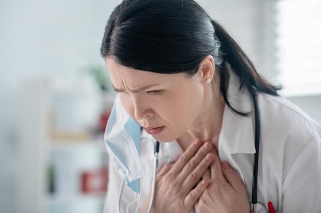 ウイルス感染。白衣を着た見栄えの悪い大人の暗い髪の女性と喉のそばで手をつないで首に聴診器