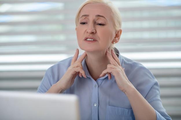 健康上の問題。ノートパソコンの前で深刻な金髪の女性が指でリンパ節を示す首の近くの手を監視しています。