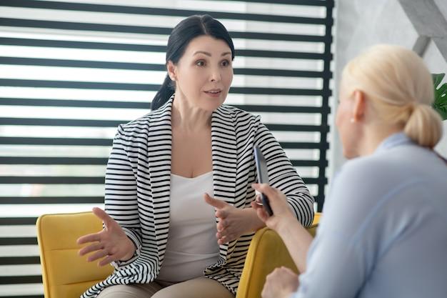 カウンセリング。彼女の手でジェスチャーを話している大人の深刻なブルネットの女性と伸ばしたスマートフォンで反対側に座っている金髪。