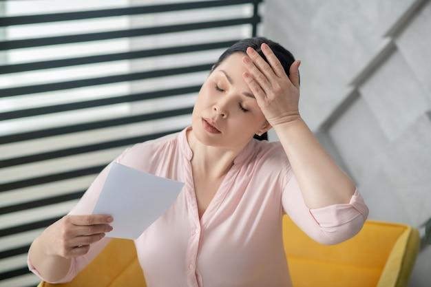 脱力感、体調不良。窓の近くの椅子に座って、目を閉じて衰弱して発汗している暗い髪の女性